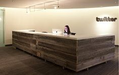 Twitter reception desk treated with contrasting finishes. Honed concrete tops including the boardroom table mfgd by Concrete Works. Concrete mix is 40% fly ash to 100% recycled aggregates.