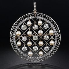 Nine European-cut diamonds and twelve natural button pearls shake from within their separate sections, and are encircled by a slender row of rose-cut diamonds, in this openwork pendant and pin, delicately handcrafted in platinum over gold - circa 1900. The nine diamonds total 5.50 carats, with original matching rose-cut diamond loop.