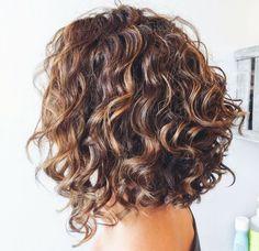 carré plongeant destructuré avec cheveux de base marron aux mèches blond cuivré et boucles en dégradé
