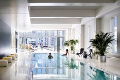 OneEleven's resort class indoor pool has a retractable wall that opens to a roof… – Sungyong Oum – pet resort White Ottoman, Pet Resort, Chicago Apartment, Rooftop Deck, Dream House Exterior, Floor To Ceiling Windows, Sliding Glass Door, Glass Doors, White Tiles
