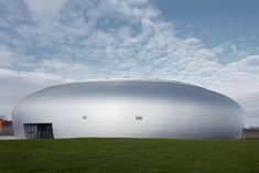 Domed sports hall by Sporadical is clad in scale-like aluminium shingles