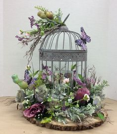 Floral design I made using wire bird cage glued to foam that was glued to log slab. Added a painted thin wood circle inside cage to cover glue. Added LED candle with mirror tiles inside cage. Added moss to cover foam. Glued flowers to foam and at top of cage as well as two butterflies.