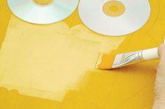Preencha toda a tela, inclusive as laterais, usando o rolinho e a tinta acrílica amarelo-ocre. Aguarde a secagem por 30 minutos. Com o lápis, transfira o molde da coruja, estendendo os galhos para as laterais da tela. Com a cola para lantejoulas, fixe os CDs nas marcações dos olhos. Use o pincel nº 410-24 e a tinta ouro para preencher todo o peitoral da coruja com movimentos de dentro para fora.