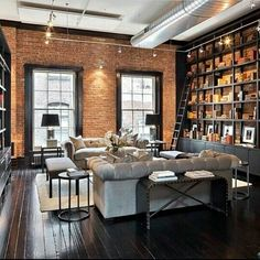 industrial loft | living room | brick walls | wall to wall built-in bookcase | sofas | dark hardwood floors