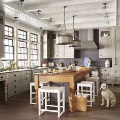 In this (supersize) galley kitchen, a teak island and two oversize galvanized fixtures above it reinforce the home's not-too-delicate, bring-on-the-wet-swimsuits vibe. The muted colors of the traditional-style cabinetry, charcoal tile, and soapstone countertop allow the nature outside to steal the show.