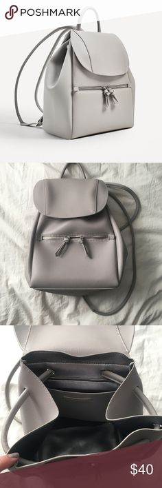 NWOT. Gray Zara backpack This backpack is super fashionable and trendy. Very chic style that can be dressed up. NEVER WORN. Amazing condition. Features a front zip pocket, inside slot pocket, and this amazing metallic interior. Drawstring and snap closure. Straps are adjustable. Faux leather. Zara Bags Backpacks