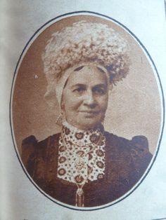 Vrouw uit West-Brabant. Zij draagt de dubbele muts met een hoge kroon. en valse lokjes, blesjes genaamd. Mode jak en een  schuifketting met kwastjes.