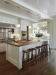 Modern cottage kitchen with glossy white beadboard ceiling and white box beams. White wood paneled center island with butcher block countertop and sawhorse counter stools. Love the chocolate wood kitchen design interior design ideas design Rustic Kitchen, New Kitchen, Kitchen Decor, Kitchen Ideas, Kitchen Designs, Craftsman Kitchen, Kitchen Layout, Kitchen Photos, Long Kitchen
