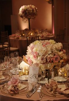 Lavender, pink, and cream centerpiece, pink linens, gold trimmed chargers and chiavari chairs.