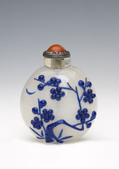 Burghley Collections | A clear glass snuff bottle, 1750-1900.  The circular bottle has a dark blue overlay which is carved to depict, on one side, glowering prunus and on the other, an inscription.  Chinese.
