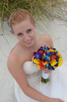 colorful beach wedding bridal bouquet with yellow calla lilies, blue bomber orchids, orange roses and greenery, Fort Walton beach weddings, photo and bouquet by Sunshine Wedding Company