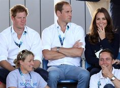 Britain's Kate Duchess of Cambridge, right, and Prince William, center, and Prince Harry, left, react as they watch the women's field hockey match bet...