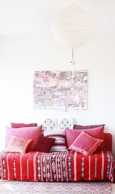 7 Essentials Every Stylish Dorm Room Needs// pink and red, paper lantern, pillows, daybed