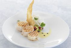 This surprising dish combines various flavours; the sweetness of scallops, the acidity of passion fruit, and a refreshing twist from the fennel, avocado and pomegranate salad. A sesame tuile provides a crunchy texture.