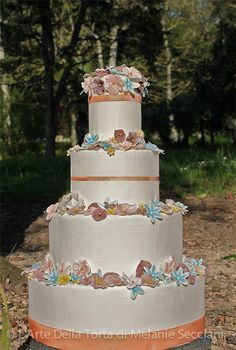 Tuscany Wedding cake by L'Arte Della Torta di Melanie Secciani in Florence, Italy. Contemporary Rustic Tuscan Wedding Cake created  in Florence, Italy.  Wedding cake is inspired by woods of Chianti. I wanted to give the cake an almost magical midsummer nights dream feel. Tiers are enrobed in linen embossed fondant, and embellished with vibrant sugar flowers and rustic painted copper sugar ribbons.