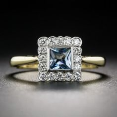 Newly crafted in platinum over 18 karat yellow gold, in London, England, in classic and enduring vintage style, this charming gemstone ring centers on a radiant square faceted aquamarine outlined by small, bright white European-cut diamonds set in a finely milgrained scalloped frame. Currently ring size 6 3/4.