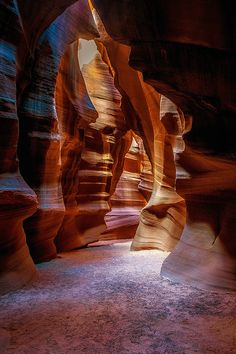 Antelope Canyon, Arizona | A slot canyon is a narrow canyon sliced through a mesa by the forces of nature. Some canyons measure less than a yard across at the top, but drop a hundred feet or more from the rim to the bottom. Slots are cut and scoured by water and wind, with the striations of the sandstone becoming almost incandescent.