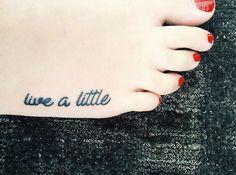"""Pequeño tatuaje en el pie que dice """"live a little"""", que significa """"vive un poco""""."""