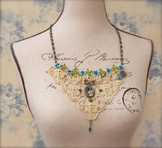 Lace statement bib, OOAK, Victorian/Shabby Chic/Mori Girl genres, with vintage European ecru lace, a silver framed Italian hand painted portrait, vintage metal/enamel buttons, and a lovely, Swarovski pearl embellished, sage green, cream, and azure blue floral trim. A sparkling, delicate pendant of Swarovski Indicolite and Air Blue Opal crystals provides a little eye catching movement. This accessory would be exquisite as part of a vintage bridal ensemble...