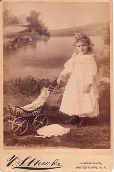 An adorable curly haired little girl poses with her doll in a stroller in front of a water scene backdrop at the studio of T. S. Hawke in Watertown, New York.