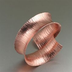 Chased Copper Anticlastic Bangle Bracelet - This eye-catching anticlastically raised handcrafted copper cuff bracelet is sure to make a statement.  Simply stunning, this bracelet features a deep textured pattern that gleams a rose gold like hue. $180 http://www.ilovecopperjewelry.com/texturized-anticlastic-copper-bracelet-1.html