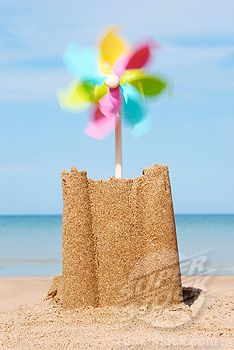 Sand castle with moving pinwheel on beach