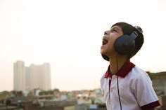 Boy singing while listening music with headphones on a roof top Roof Top, Singing, Headphones, Portrait, Boys, Music, Headset, Baby Boys, Musica