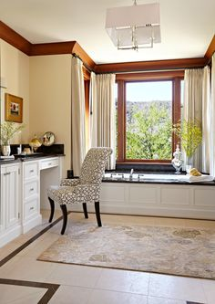 A soft beige rug sits atop creamy beige bathroom tiles, while window coverings seamlessly blend into the light neutral walls. A patterned chair slides into a vanity that matches the tub. #bathroomideas #bathroomcolorschemes #beigebathrooms #bathroomdecor #remodel #bhg