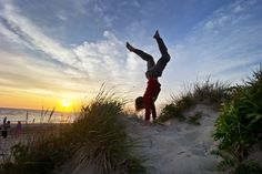"Wellfleet, MA- July 1, 2014- Globe Staff Photo by Stan Grossfeld- Damon Wolf, 13, New Paltz, N.Y. does a handstand as the sun sets into Cape Cod Bay in Wellfleet.Damon Wolf, 13, New Paltz, N.Y. ""The sun kind of got low enough in the sky and it just illuminated everything and the colors of the dunes were really saturated and really popped out at me and looked awesome. It just made me extremely happy. I love life, life is awesome. This is such a beautiful place to be in the entire world…"