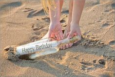 Picture of Happy birthday message in a wine bottle on the beach.