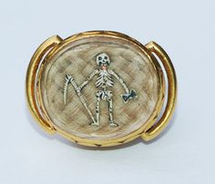 Stuart Crystal Skeleton Slide - From a private collection, where it has been for the past thirty years, a rare Stuart crystal Memento Mori slide, circa 1680. The gold slide contains a compartment with a ground of woven hair, overlaid with a brightly enamelled skeleton holding symbols of mortality, a scythe and an hourglass.