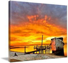 """""""Old Boat Yellow Red Sunrise Fine Art Giclee Prints"""" by Eszra Tanner, navarre, fl // a <b>dark red</b> sunsrise behind an old boat and broken pier.  Landscape taken near <i>Navarre Beach, Florida</i>.  Fine art giclee prints available. // Imagekind.com -- Buy stunning fine art prints, framed prints and canvas prints directly from independent working artists and photographers."""