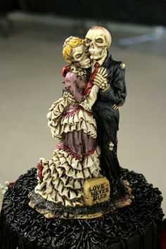 A closeup of a corpse bride and groom halloween wedding cake topper