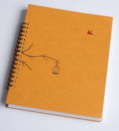 Spiral bound letterpress notebook. Letterpress cover printed blind deboss stars, copper ink branch with cage, and red pepper ink bird. Size: 6 inches wide by 7 1/2 inches tall Paper: Mohawk Loop Inside pages: approx 50, not lined