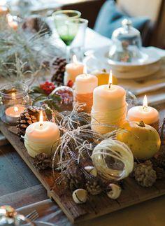 Un centro de velas ilumina los caminos de lino que dejan ver la mesa de madera antigua, bruñida por el tiempo. Bandejas de madera rústica