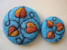 Blue felt buttons with orange/gold heart shaped leaves and embroidery.
