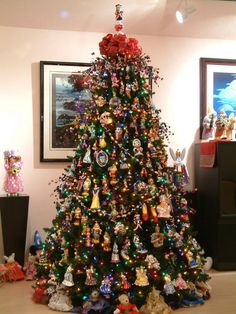 Tall Christmas tree filled with Christopher Radko collectible glass Disney ornaments