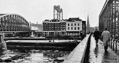 Een foto op de Willemsbrug met links de spoorbrug. Tussen de bruggen in zien we een stukje van de Maaskade en op de achtergrond de mooie Hef en de Rooms-Katholieke kerk op het Stieltjesplein. Waarschijnlijk komt de foto uit de winter van 1948-1949. Het is een archieffoto van het Algemeen Dagblad