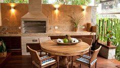 Na outra ponta do ambiente, a churrasqueira de concreto revestida de cerâmica filetada. Na mesa, estampa dos assentos também remete ao ambiente da praia Foto: Renata Missagia