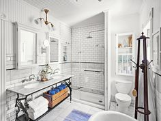 A vintage iron vanity and white subway tiles transform old, drab facilities into a period-perfect Victorian bathroom.