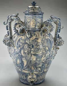 Apothecary jar, Italy, 1730-1750 This apothecary jar is illustrated with scenes of a circumcision and three devils' heads. Entwined snakes form the handles. The devil's head at the base appears to be a dispensing hole for the contents of this large jar.