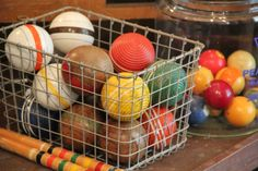 A bowl, wire basket or antique counter jar filled with croquet or pool balls adds colorful interest to a room.  We usually add a quick coat of clear Briwax to clean them up and bring out the natural color of the wood and old paint.  NOTE: We have green & yellow like the picture and possibly more of the set like the mallets shown. LIZ kept 2 ridged balls