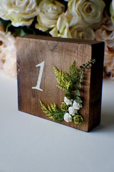 Beautiful wooden table numbers. Made with solid stained wood, decorated with artificial flowers. They can be made one r double sided. They will make a great addition to your wedding table decor and will look very lovely against flower centerpieces, candles glassware.  sizes