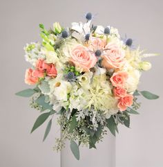 stunning garden: a gorgeous and full bouquet of white hydrangea, freesia and astilbe with peach alejandro roses, ilse spray roses, thistle, fragrant white stock, seeded eucalyptus and dusty miller.