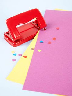 Shiny red hole punch which punches heart-shaped holes, resulting in heart-shaped confetti too.