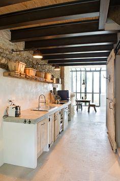 Una reforma de estilo industrial para un espacio estrecho y profundo. Cocina de obra en edificio de piedra