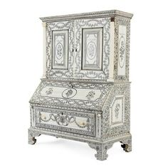 Anglo-Indian Ivory, Penwork and Sandalwood Diminutive Bureau Bookcase  Vizagapatam, circa 1790, the locks and hinges English silver, london, 1791  With a pair of paneled cupboard doors flanked by fluted stiles, opening to reveal an arrangement of drawers and valenced pigeonholes above a hinged flap opening to a fitted interior and one long drawer, raised on bracket feet, the whole decorated with bouquets within scrolling foliate borders.