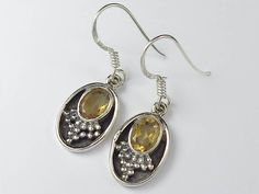 Beautiful sterling silver earrings decorated with faceted yellow citrine stone with fine details throughout.