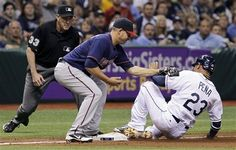 Tampa Bay Rays' Carlos Pena (23) slides safely into third base ahead of the tag by Minnesota Twins third baseman Danny Valencia (22) during the sixth inning of a baseball game