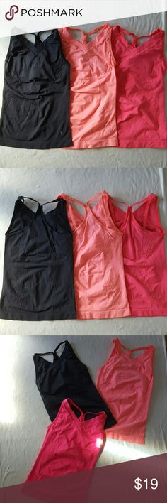 Lot of 3 seamless workout tops Lot of 3 seamless cami workout tops in xsmall. Pink, coral, and grey. Coral has light stains on side (please see pic 4). Built in shelf bra, no padding. Very comfy and stretchy. Each worn once. Old Navy Tops Tank Tops